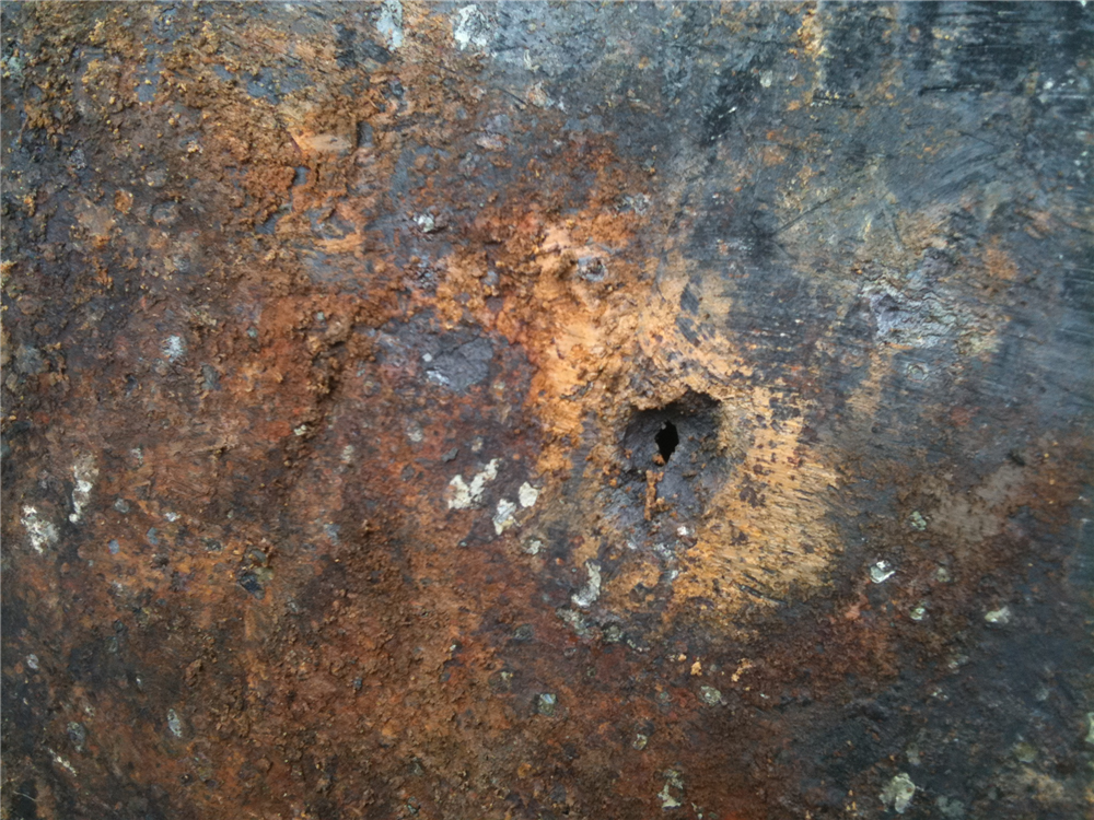 Corrosion hole noted in side of tank. A more serious concern would be if an oil stained area was present on the outside of the tank.