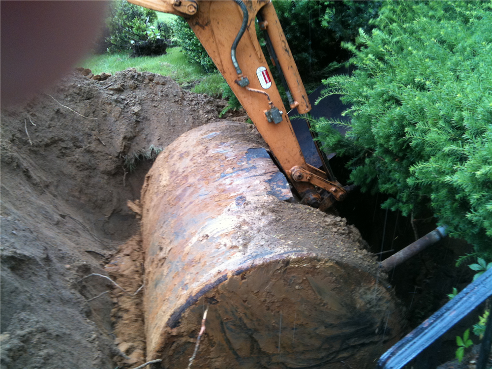 Oil tank being removed from the ground.